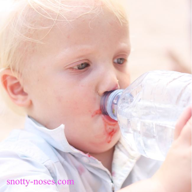 Help Your Children Form Healthy Eating Habits. My son drinking from a water bottle with strawberry juice around his mouth.